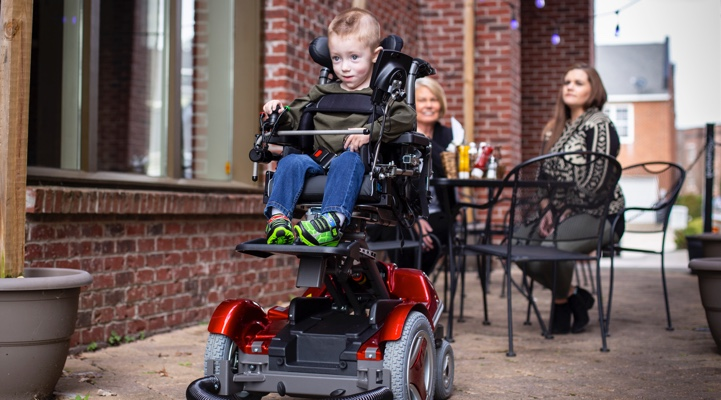 a child moving around in a wheelchair
