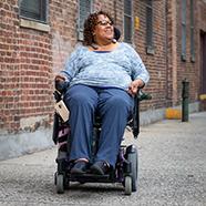 Happy woman riding down an urban sidewalk in her power chair.