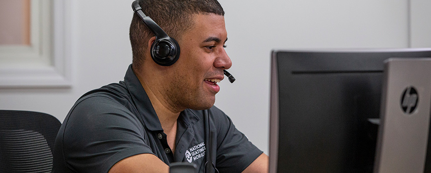 A smiling customer service representative on the phone helping a customer.