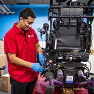 A NSM technician repairing a power chair.