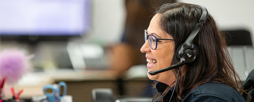 Customer service lady smiling on the phone with a customer.