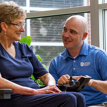 A NSM technician helping an elderly woman get familiar with her new power chair.